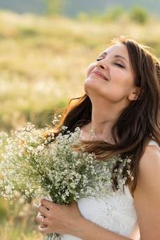 Vista laterale della donna che posa in natura con i fiori