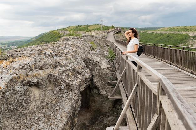 Vista laterale della donna che posa in natura sul ponte