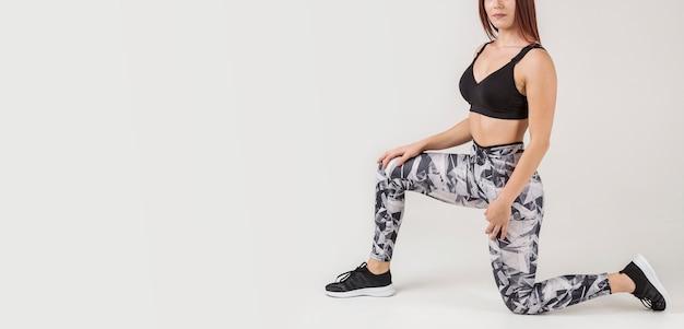 Vista laterale della donna che posa nel athleisure con lo spazio della copia