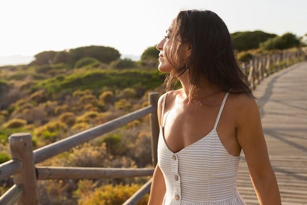 Vista laterale della donna che posa sul ponte in natura