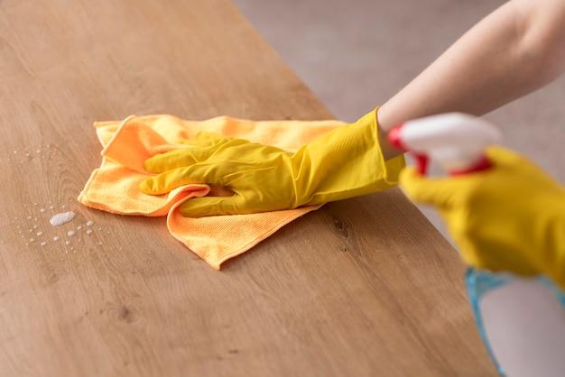 Vista laterale della donna che pulisce superficie di legno con il panno