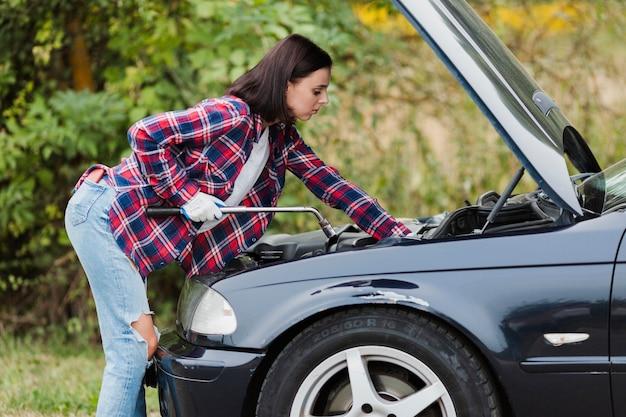 Vista laterale della donna che ripara il motore di automobile