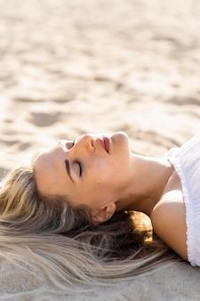 Vista laterale della donna che si distende sulle sabbie della spiaggia