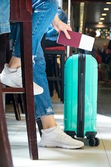 Vista laterale della donna che si siede nell'aeroporto