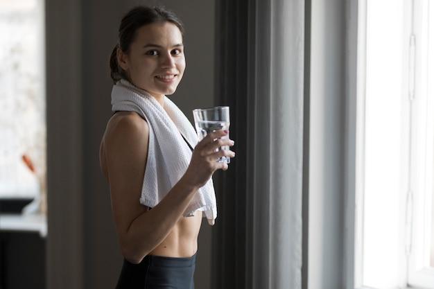 Vista laterale della donna che sorride e che tiene un bicchiere d'acqua