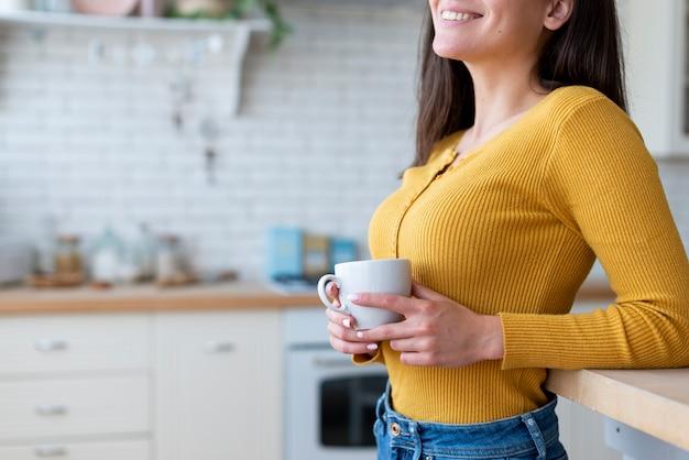 Vista laterale della donna che tiene una tazza