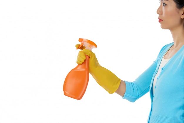 Vista laterale della donna che usando il pulitore dello spruzzo contro il copyspace bianco del fondo