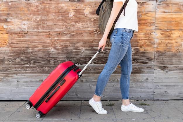 Vista laterale della donna con i suoi bagagli
