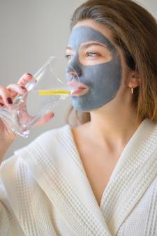 Vista laterale della donna con l'acqua potabile della maschera di protezione con il limone