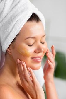 Vista laterale della donna con l'asciugamano sulla testa che applica la cura della pelle