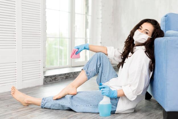 Vista laterale della donna con la maschera che posa mentre pulendo