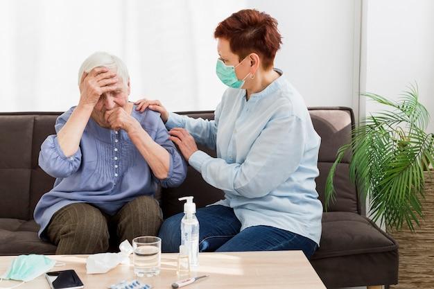 Vista laterale della donna con la maschera medica che prende cura di una donna più anziana a casa