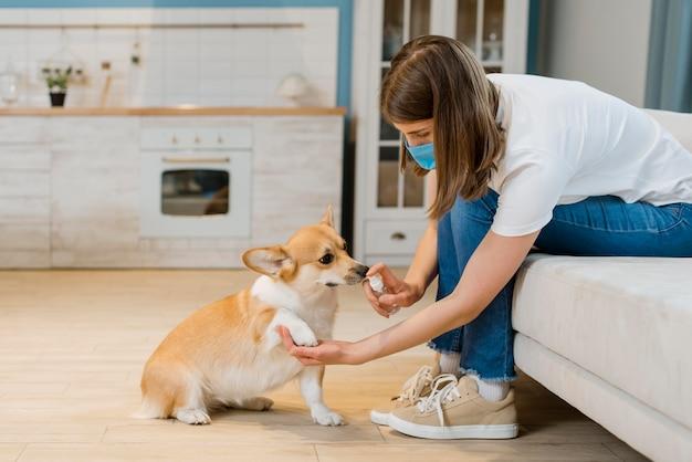 Vista laterale della donna con la mascherina medica che disinfetta le zampe del suo cane