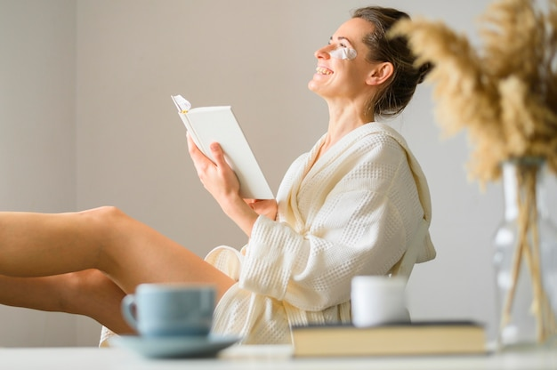 Vista laterale della donna con le bende sull'occhio che legge un libro