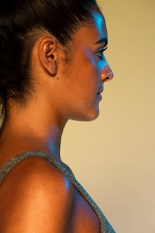 Vista laterale della donna con sfondo giallo