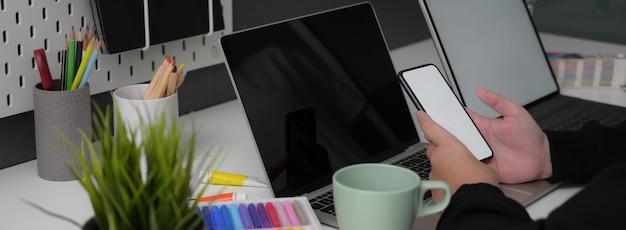 Vista laterale della donna di affari che lavora con lo smartphone del modello sulla tavola bianca