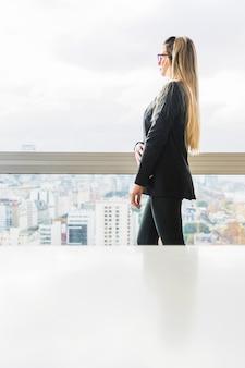 Vista laterale della donna di affari che sta vicino al vetro di finestra nell'ufficio