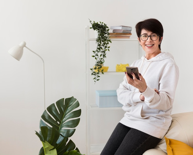 Vista laterale della donna di smiley con lo smartphone
