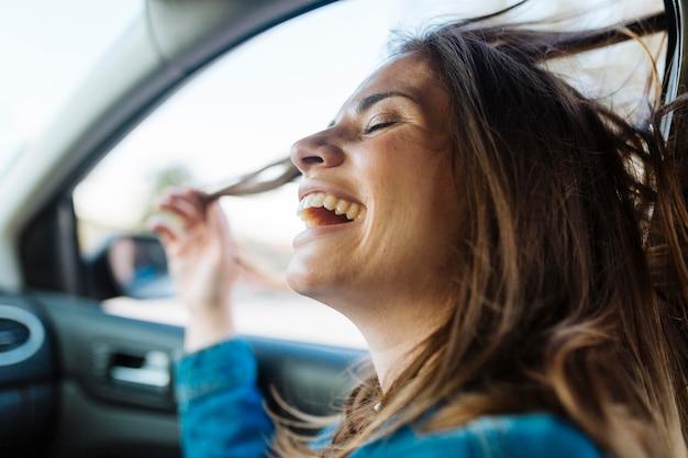 Vista laterale della donna felice che gode di un giro in macchina