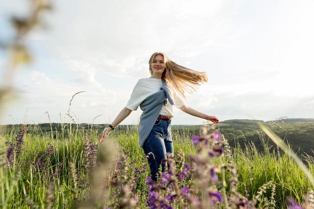 Vista laterale della donna felice che posa attraverso il campo