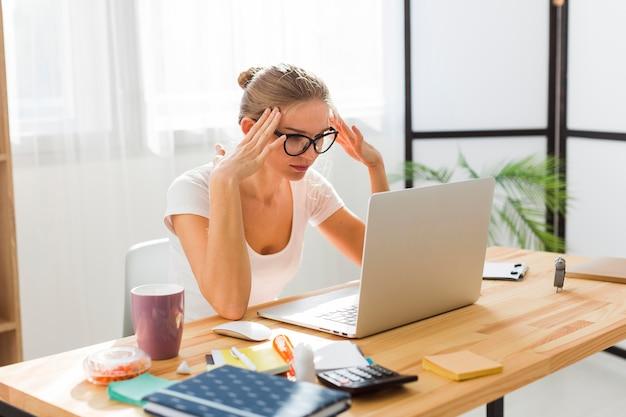 Vista laterale della donna frustrata che lavora dalla casa
