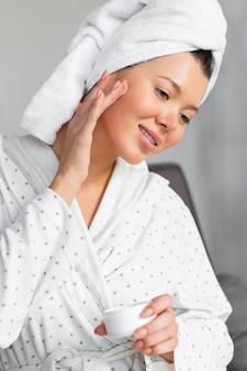 Vista laterale della donna in accappatoio e asciugamano che applica la crema