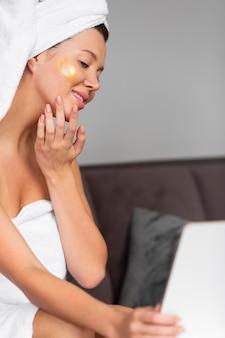 Vista laterale della donna in asciugamano che applica la cura della pelle a casa