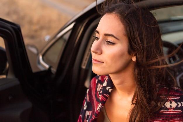Vista laterale della donna in avventura con auto