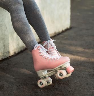 Vista laterale della donna in calze con pattini a rotelle