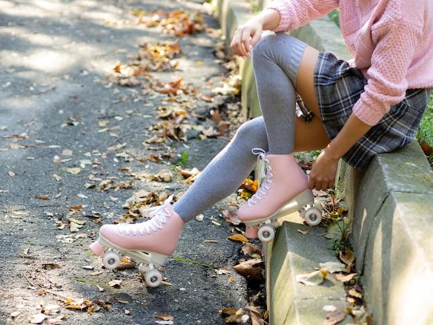 Vista laterale della donna in calze e pattini a rotelle