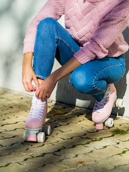 Vista laterale della donna in jeans con pattini a rotelle