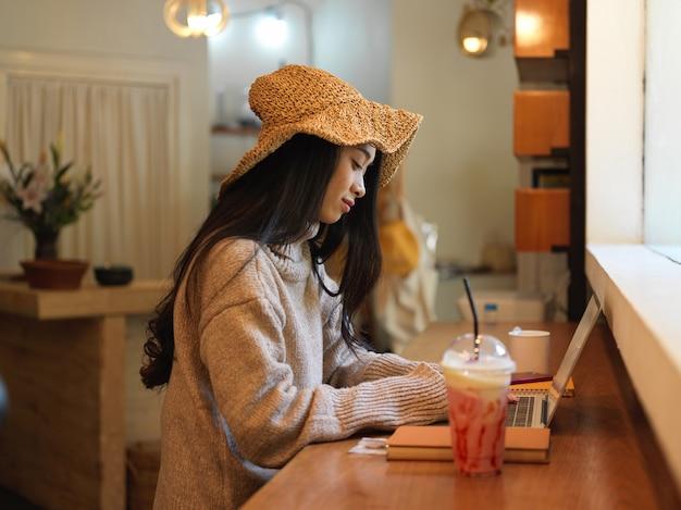 Vista laterale della donna in maglione e cappello lavorando con laptop e articoli di cancelleria mentre è seduto al bancone della caffetteria