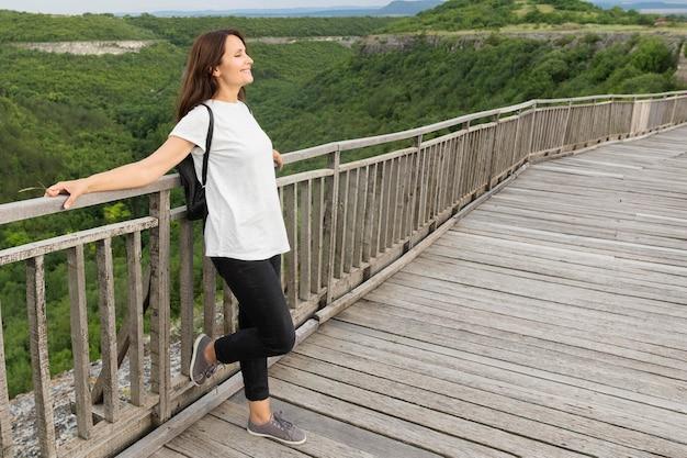 Vista laterale della donna in natura che posa sul ponte