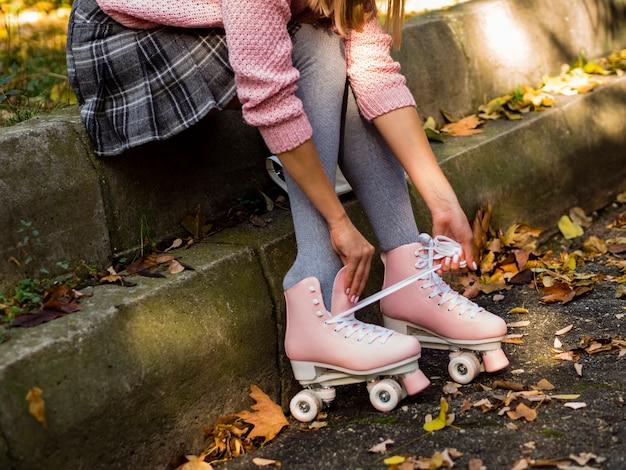 Vista laterale della donna in pattini a rotelle e foglie