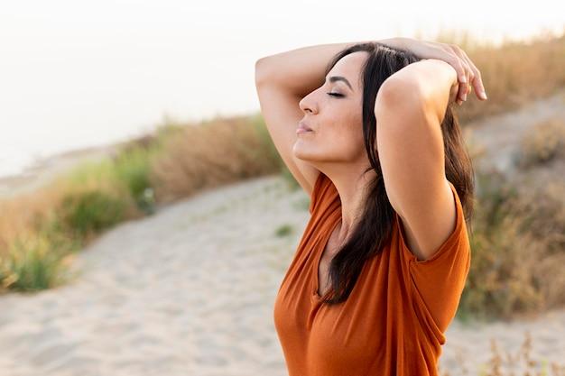 Vista laterale della donna in posa spensierata in spiaggia