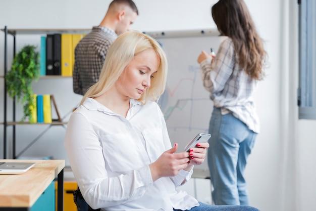 Vista laterale della donna in sedia a rotelle che esamina telefono nell'ufficio