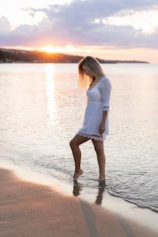 Vista laterale della donna in spiaggia al tramonto