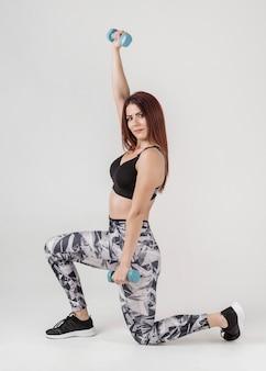 Vista laterale della donna in un ginocchio che si esercita con i pesi