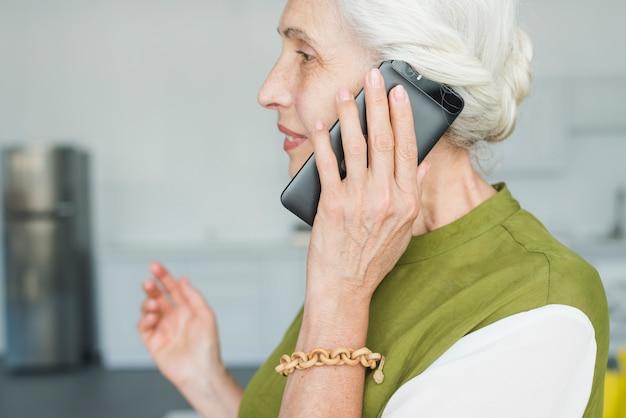 Vista laterale della donna maggiore che parla sul telefono cellulare