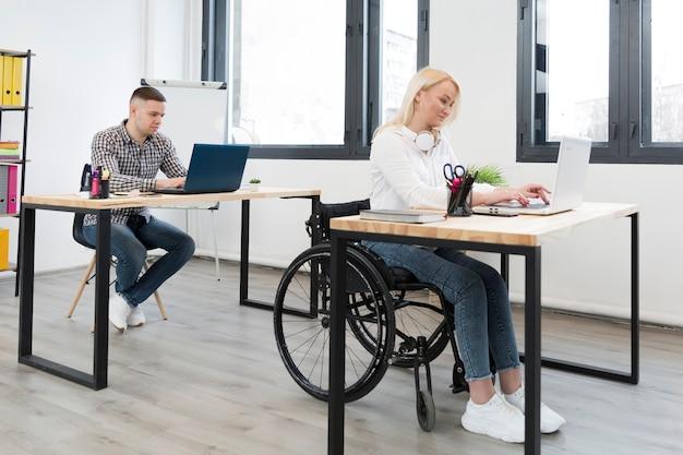 Vista laterale della donna nel funzionamento della sedia a rotelle il suo scrittorio