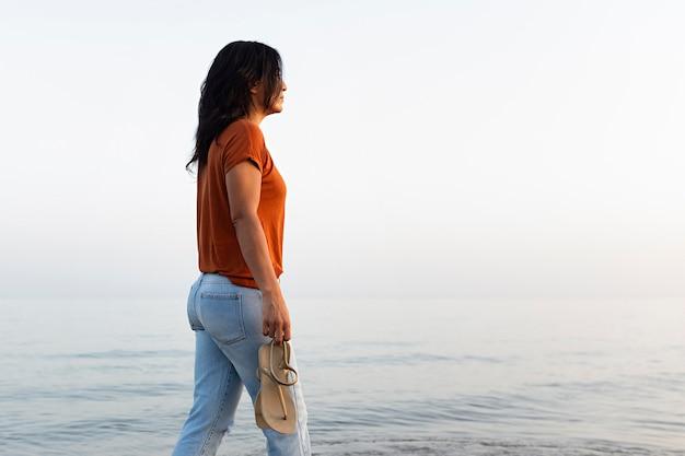 Vista laterale della donna pensierosa che fa una passeggiata sulla spiaggia