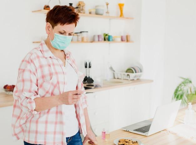 Vista laterale della donna più anziana che indossa maschera medica e che esamina termometro