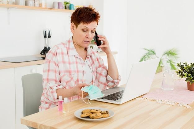 Vista laterale della donna più anziana che parla sulla maschera medica dell'intera tenuta del telefono