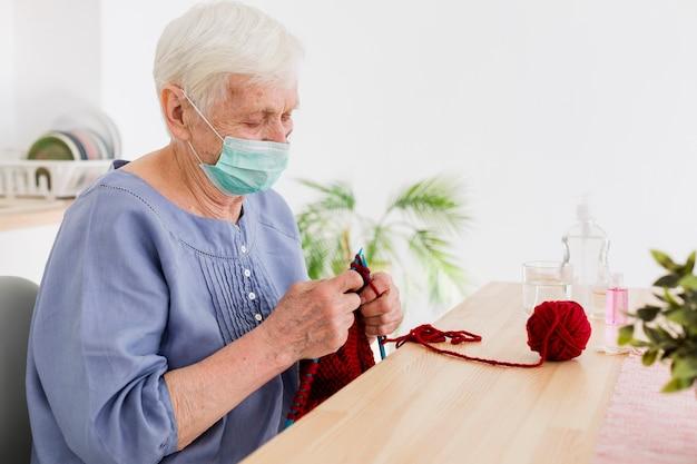 Vista laterale della donna più anziana con la maschera medica che tricotta a casa