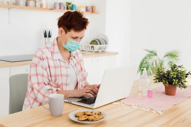 Vista laterale della donna più anziana con la mascherina medica che lavora dalla casa