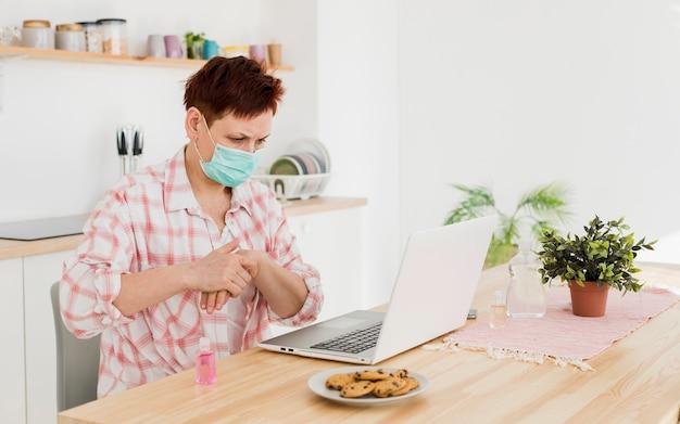 Vista laterale della donna più anziana con maschera medica utilizzando disinfettante per le mani prima di lavorare sul computer portatile