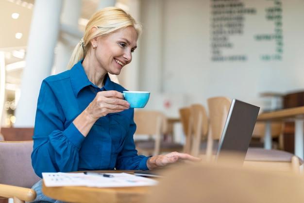 Vista laterale della donna più anziana felice di affari che mangia tazza di caffè e che lavora al computer portatile