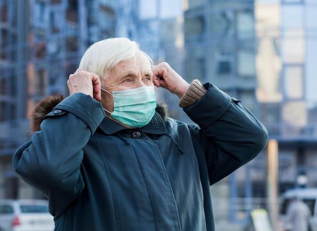 Vista laterale della donna più anziana nella città che indossa maschera medica