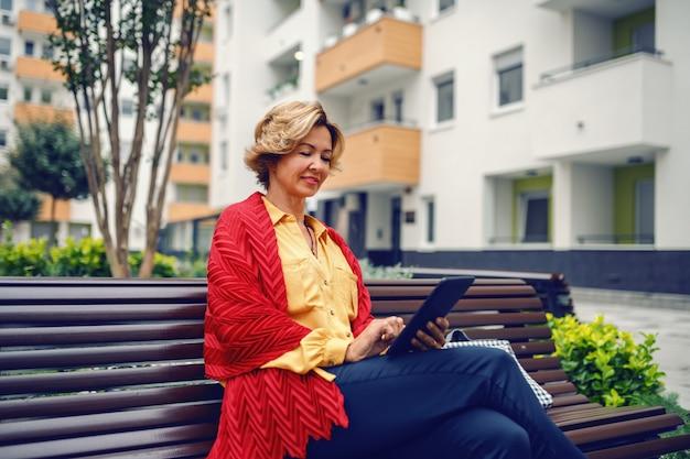 Vista laterale della donna senior alla moda caucasica sorridente affascinante con capelli corti biondi che si siedono sul banco