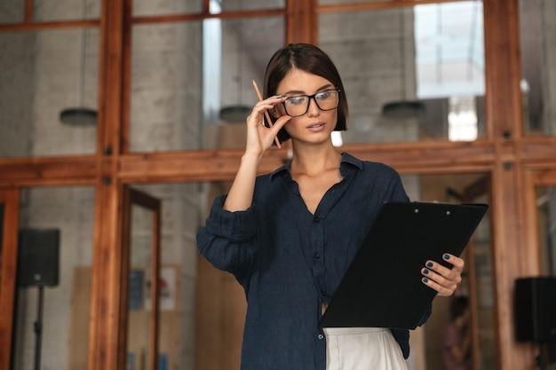 Vista laterale della donna seria di affari in occhiali nell'ufficio di lavoro co sopra la porta di vetro